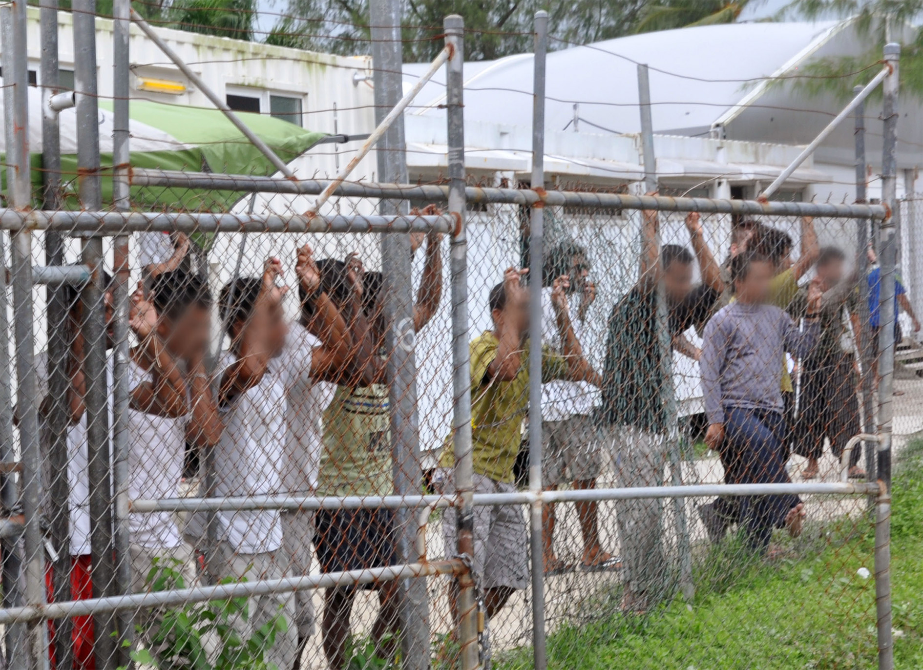 Asylum seekers look at the media from behind a fence at the Manus Island detention centre, Papua New Guinea in this picture taken 21 March 2014. This is image is supplied from source with faces digitally blurred.