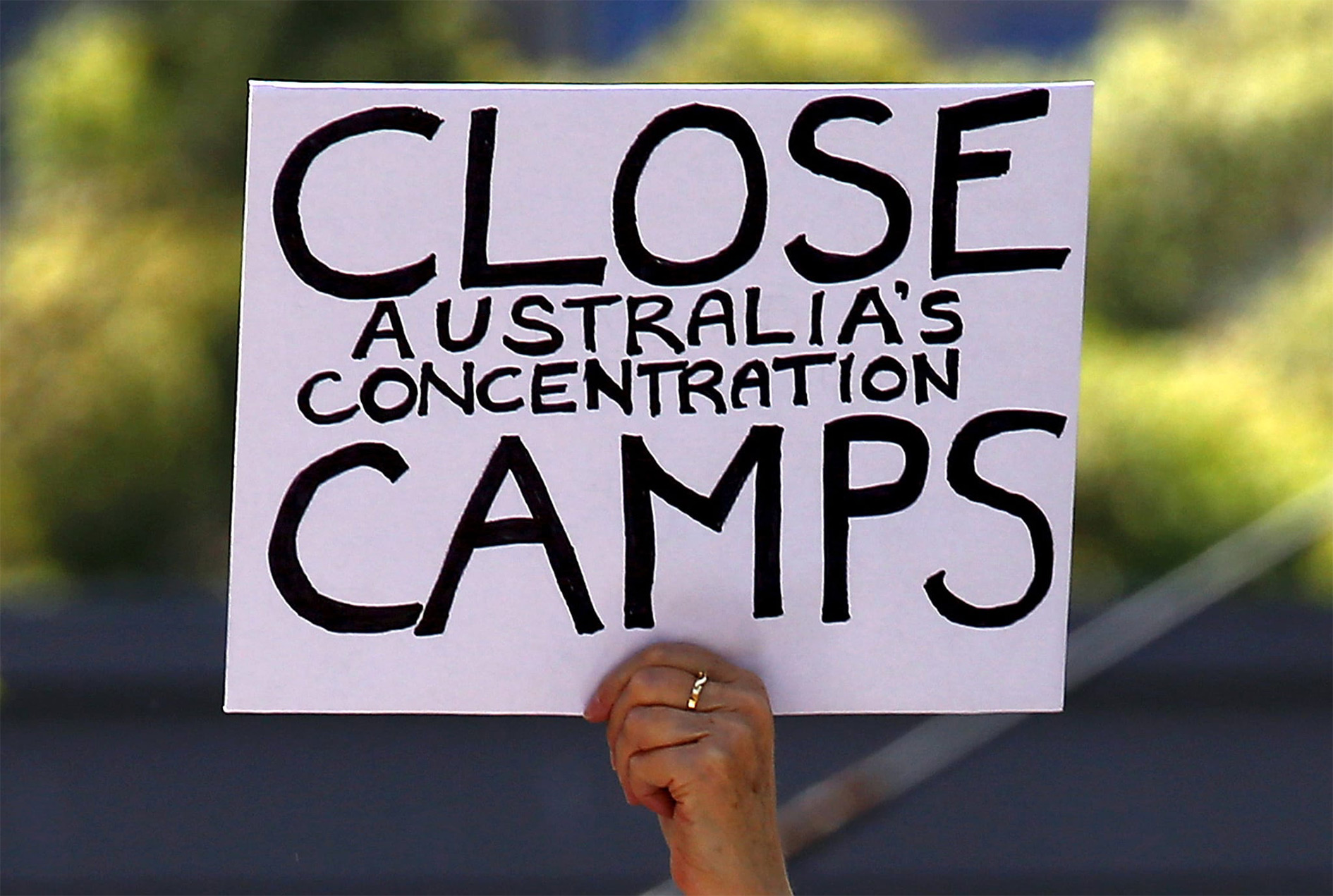 A protester holds a placard during a rally in support of refugees in central Sydney, Australia, 19 October 2015.