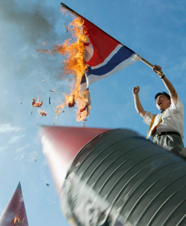 Flaming fury: A South Korean man burns the North Korean flag in protest at the country's 2003 announcement that it is developing nuclear weapons.