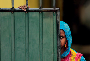Still wary: a Muslim woman peers around a gate in Aluthgama, a town 50 kilometres south of Colombo. At least three Muslims were killed there in 2014 in a clash with a rightwing Buddhist group.Photo: Eranga Jayawardena/AP/Press Association Images