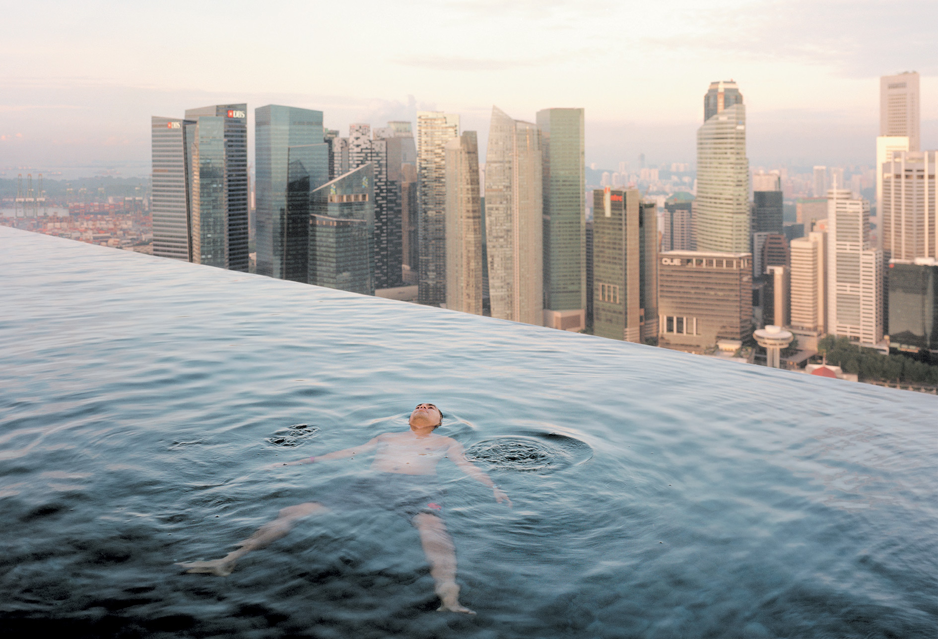 Floating on top of the world – a well-heeled client enjoys himself in the infinity pool of the luxurious Marina Bay Sands hotel overlooking Singapore'sfinancial district (where discretion isguaranteed).