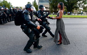 Sometimes the unarmed, but brave, have the greater power. This protester is confronting Louisiana police after the killing by police of yet another African-American youth.Photo: Jonathan Bachman/Reuters
