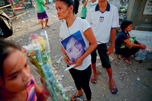 Fond hopes that die: Angelo Lafuente's mother visits his grave. His body, riddled with bullets and covered in torture marks, was found by a filthy river that feeds into the Manila bay. She blames the police for his death.