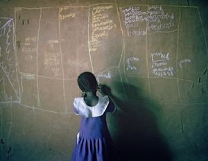 A child practises writing the days of the week on the wall of her house in Meme, Cameroon.