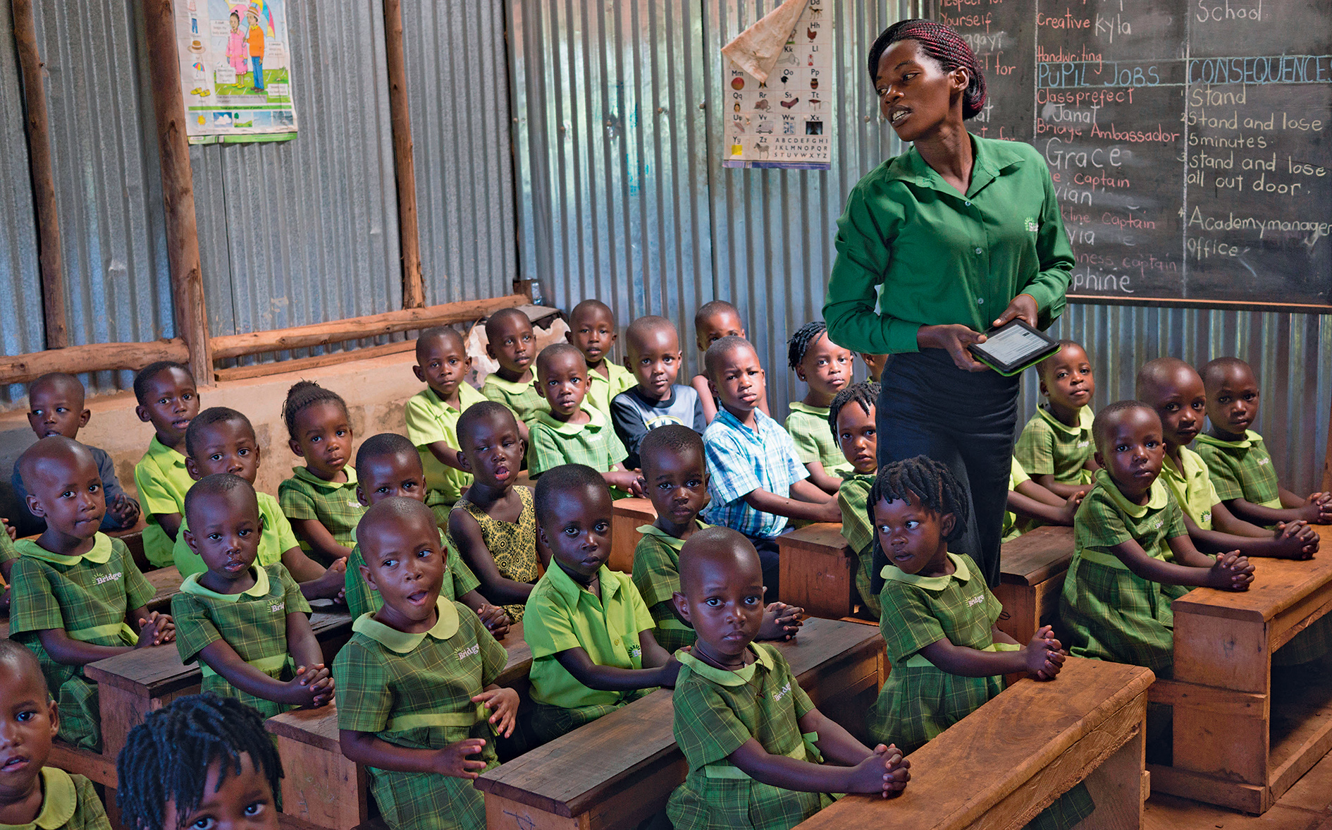 Education by e-book? A teacher and her class at low-cost private school  Bridge in Mpigi, Uganda.