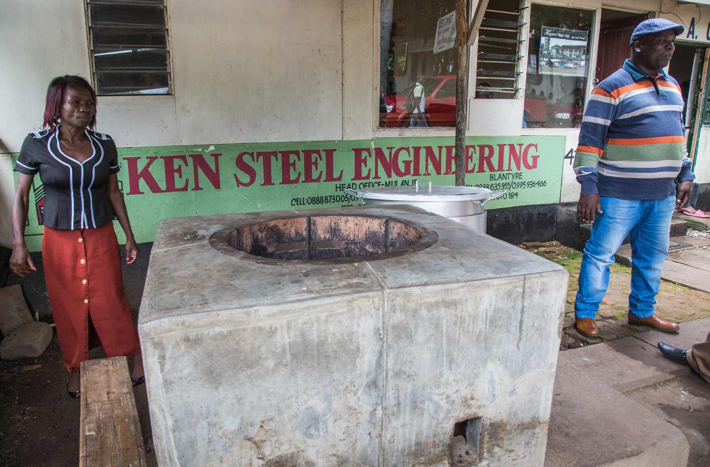 Ken Chilewe (right) is the most successful man in Mulanje – his business, Ken Steel Engineering, makes millions of dollars selling cookstoves. In front of his shop he built a rocket stove intended for serious cooks: the stove can hold a large pot for water; enough for the whole family.