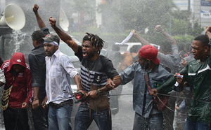 University students from the Free Papua Organization and the Papua Student Alliance resist police using water cannons during a protest in Jakarta, 1 December 2016.