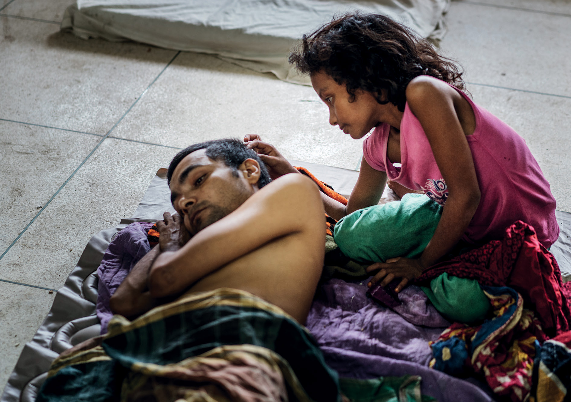Rohingya girl at Sadar Hospital caring for her dad.