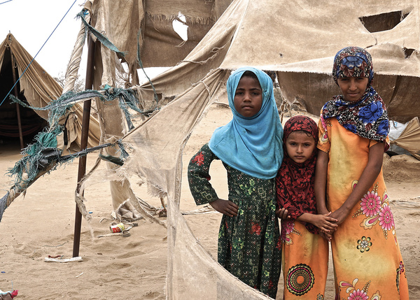 These three Yemeni girls are among the 3.1 million people displaced by the war. They stand by the shredded remains of their tents in Abs settlement, which is regularly damaged by passing sandstorms. Photo: Giles Clarke, UN OCHA / Getty Images