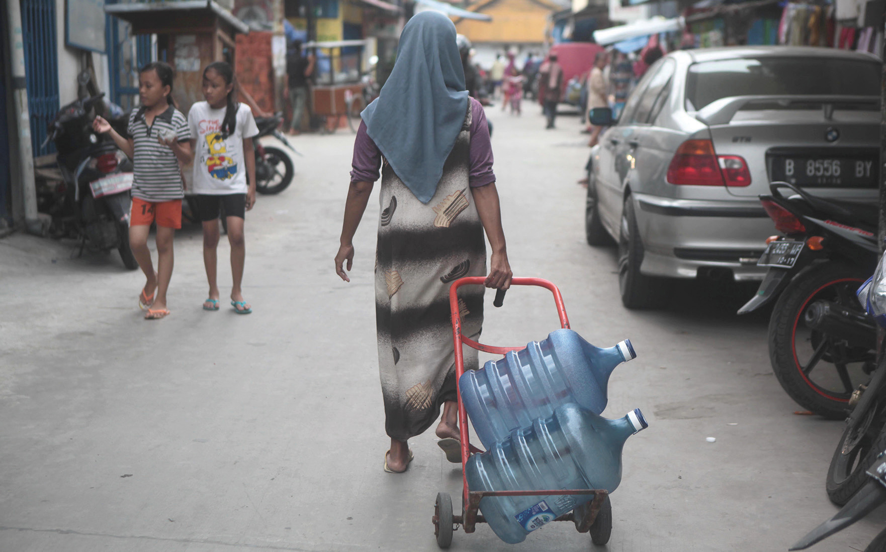 A drinking water vendor sets off, looking for customers in Jakarta's poorer neighbourhoods.