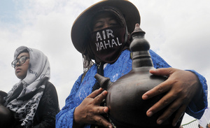 Displaying a traditional water jug, these women join a rally against corporate control of the water supply in Jakarta on International Water Day.
