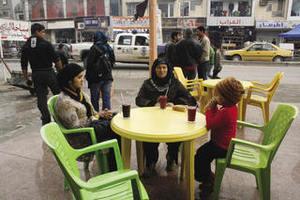 Three generations of women at a juice bar at Karradeh.