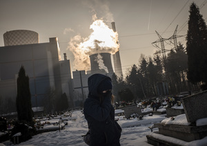 Winter wind blows from Bedzin's coal-fuelled electricity plant, stoking clouds of smog, while a woman visits the city's municipal cemetery. Photo: Violeta Santos Moura