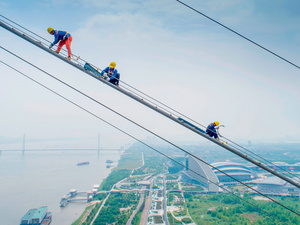 Workers labouring on a suspension bridge across the Yangtze River in May 2018.Photo: AFP/Getty Images