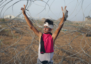 A protester stands defiantly at the fence dividing Gaza from Israel in May 2018.