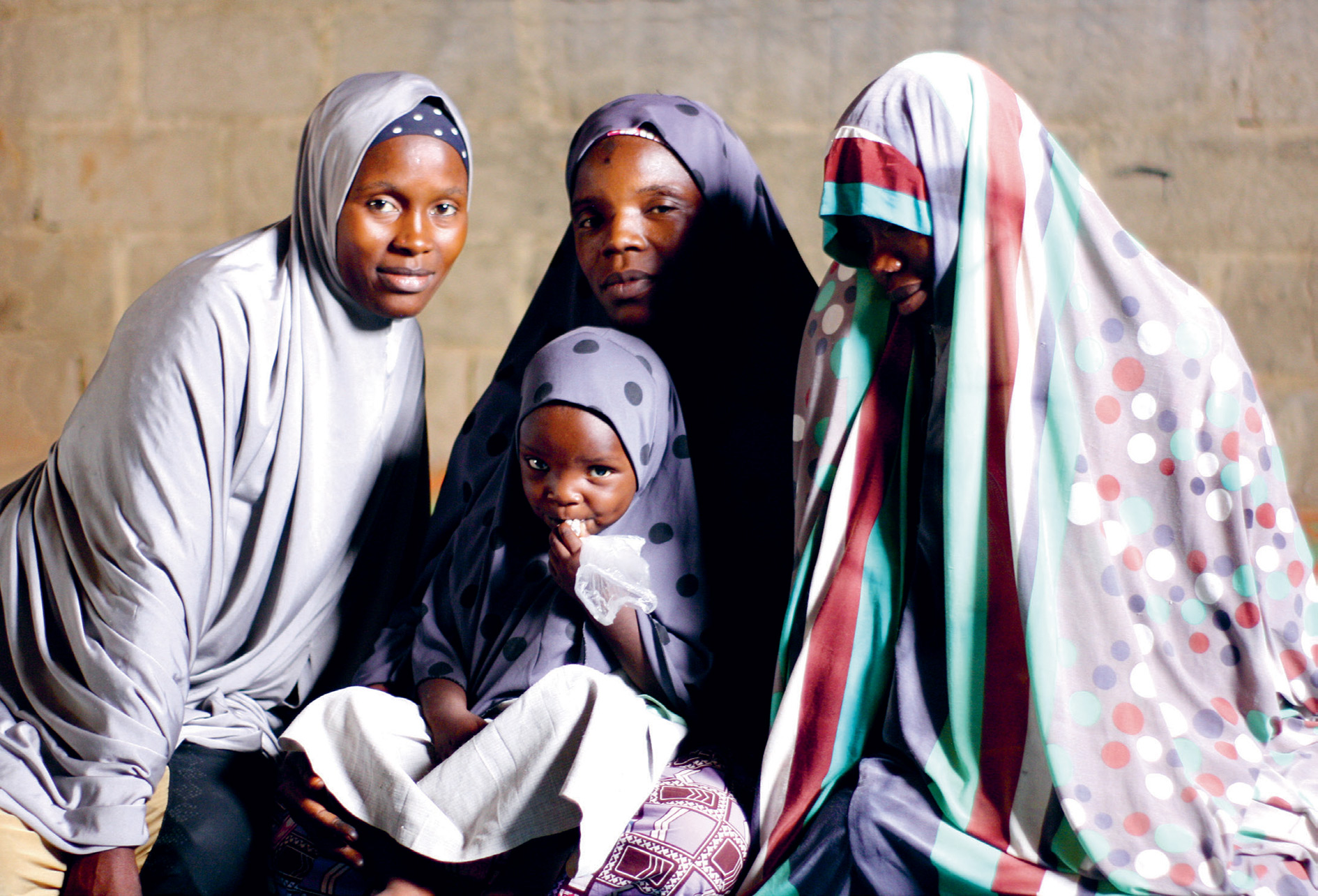 All together now – the younger sisters of Ramatu Hassan (centre) have welcomed her and her daughter back since her escape from Boko Haram.