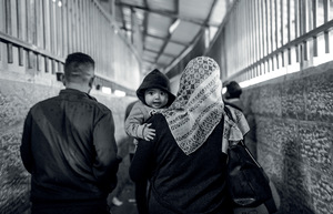 A Palestinian woman crosses 'Checkpoint 300' with her child. She is one of the few women making the morning crossing from Bethlehem to Israel – those who do, often sell vegetables and herbs in the old city of Jerusalem. Women, students and those seeking medical care in Israel or East Jerusalem should pass through a distinct 'humanitarian lane' but it is often closed, leaving them no choice but to use the crowded male workers' line.Photo: Anne Paq / Active Stills