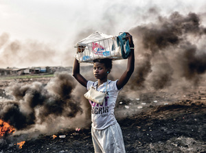 A young girl stands defiantly amid the Agbogbloshie dump's burning fields near Accra – clouds of toxic smoke rising behind her. From dusk until dawn, workers – usually young, male migrants from Ghana's northern Tamale region – burn automobile parts and electronic waste in order to reveal their copper components in exchange for money for food. According to the Seattle-based NGO, Basel Action Network, millions of tonnes of e-waste from industrialized nations are 'processed' at Agbogbloshie each year. Photo: Benjamin Lowy/Getty