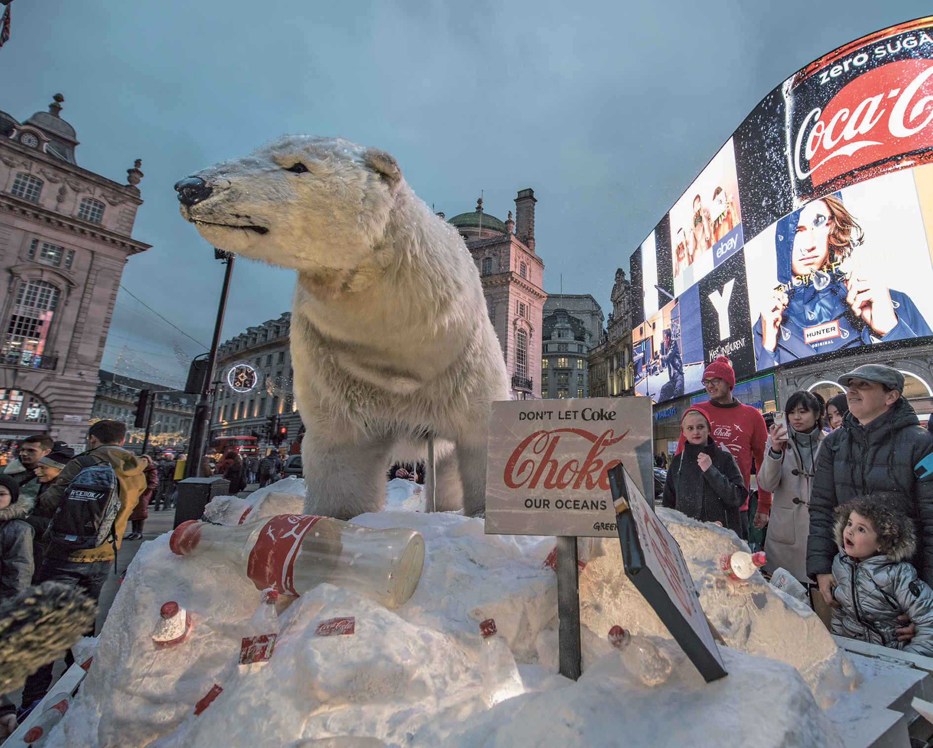 Paula, the lifesize Greenpeace polar bear puppet, shows up at Piccadilly Circus, London, to hijack Coke's advertising screen, December 2017. Coca-Cola has an enormous plastic footprint.