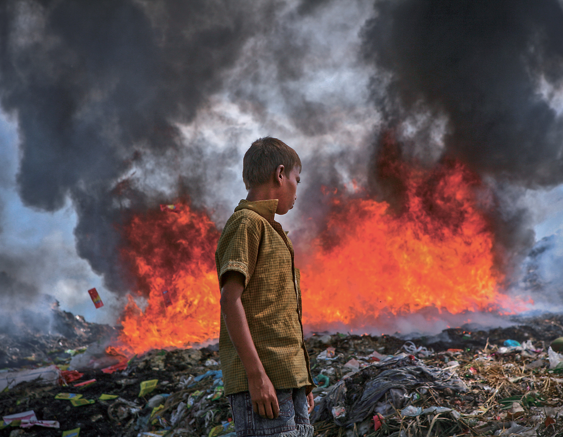 This young garbage picker continues his search for saleable items, as part of the permanent dump in Sylhet, east Bangladesh, goes up in flames.  Spontaneous fires in open dumps are a common problem.