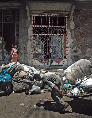 Left: Rumani, a Coptic Zabaleen, pulls his cart full of garbage outside his home in Manshiyat Naser (or Garbage City) in Cairo. Photo: Marco Bulgarelli/Gamma-Rapho via Getty