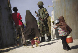 Too little, too late? Children walk past an African Union Mission soldier from Uganda at a food distribution centre in Mogadishu.