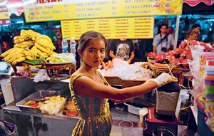 A trader blitzes up a fruit smoothie on Khao San Road, Bangkok – a vibrant street market that is threatened by gentrification.Photo: Parkerphotography / Alamy