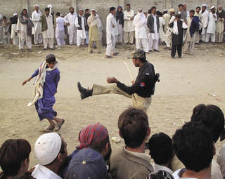 Big bully: a police officer kicks a boy to force him back in line at a food distribution point for people feeling a military offensive in South Waziristan.