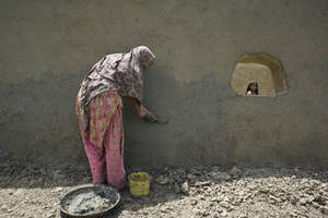 Starting over: a woman plasters the new home she has built.Iva Zimova / Panos
