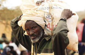 A Somali man carries food from the World Food Programme distribution centre at a refugee camp near the Kenya-Somalia border, August 2011.Thomas Mukoya / Reuters
