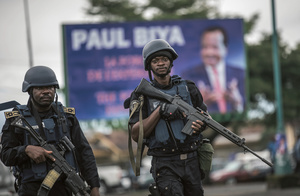Armed enforcers: members of the Cameroonian national police force patrol a square in the majority anglophone southwest province capital Buea during a political rally of President Paul Biya's ruling CPDM party. Photo: Marco Longari/AFP/Getty