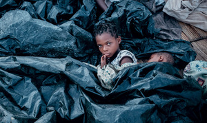 Cyclone Idai survivor Enia Joaquin Luis, 11, wakes up beside her sister Luisa, 6 – both enveloped by plastic sheeting in Buzi, Mozambique.Photo: YASUYOSHI CHIBA/AFP/Getty