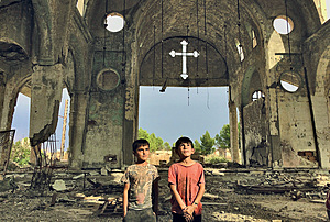 Displaced Syrian Kurdish boys stop at a derelict church in Tel Nasri searching for refuge.Photo: Karlos Zurutuza