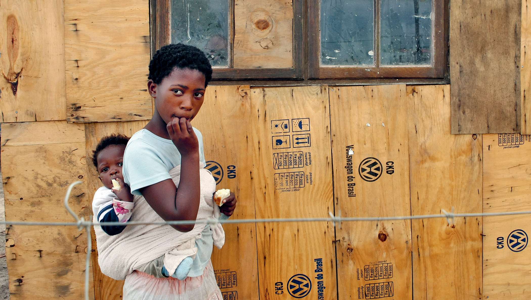 Wary looks: Ntombekhaya Sobuza and little sister Asanele outside their shack constructed from packaging materials from a Volkswagen plant, on the outskirts of Port Elizabeth, South Africa.