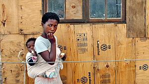 Wary looks: Ntombekhaya Sobuza and little sister Asanele outside their shack constructed from packaging materials from a Volkswagen plant, on the outskirts of Port Elizabeth, South Africa.Photo: James Oatway/Panos