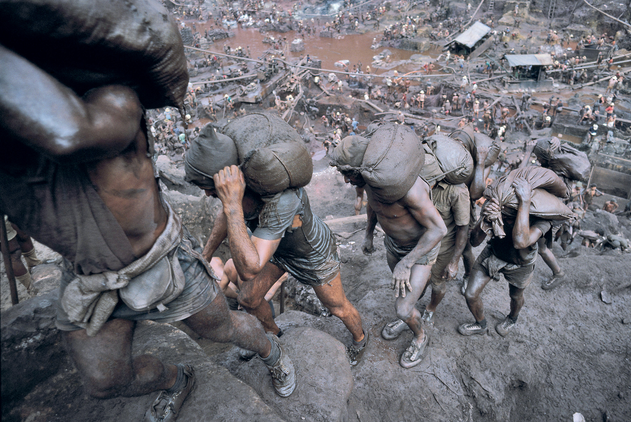 Hell on earth: the vast open-pit Serra Pelada goldmine in Brazil, 1985. Some 100,000 diggers were employed, each carrying 20-kilo sacks of ore up 400 metres via muddy steps and wood and rope ladders. Violence and deaths were commonplace.
