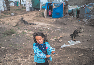 Refugees stranded: a little girl stands by the barbed-wire fence in a temporary tent camp near the overcrowded Moria camp on the Greek island of Lesvos.Photo: Angelos Tzortzinis/PA