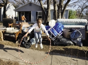 Frozen mid-jump in a 2008 snapshot of the US housing crisis: this girl's family's belongings lie on the sidewalk, following their eviction from their home in Waco, Texas. Her four siblings are not in the frame.Larry Downing / Reuters