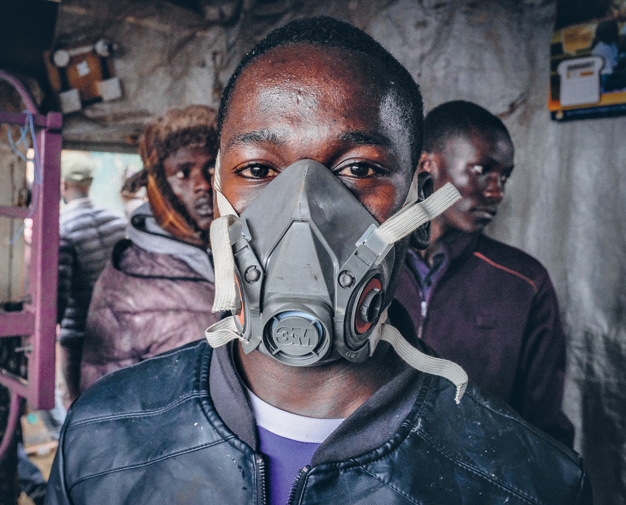 A young boy wears a gas mask to protect himself from the fumes during a fire in Kibera, the largest slum in Nairobi, Kenya.