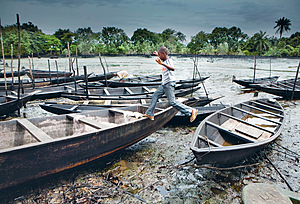 Opposite page: Child's play – a boy jumps across boats wedged on a mixture of crude oil, water and sand, near Bodo in the Niger Delta. Oil production is a major pollutant in the area.Photo: Petterik Wiggers/Panos