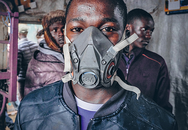 A young boy wears a gas mask to protect himself from the fumes during a fire in Kibera, the largest slum in Nairobi, Kenya. Photo: Donwilson Odhiambo/Sopa Images/Lightrocket via Getty Images