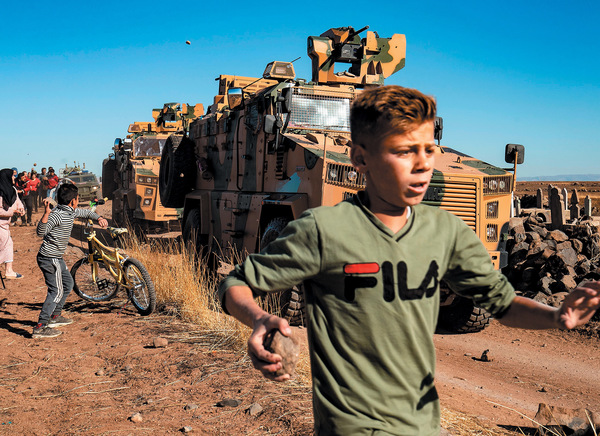 Get out! Young Kurds confront a Turkish military vehicle on patrol in northern Syria after Turkey's invasion.