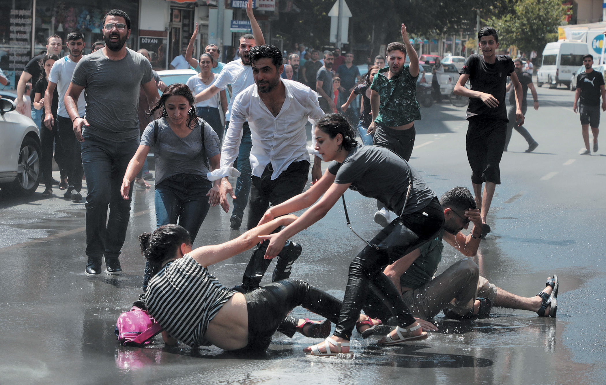 Protesters against the replacement of Kurdish mayors with state officials help each other after a water-cannon assault by Turkish police in Diyarbakir.