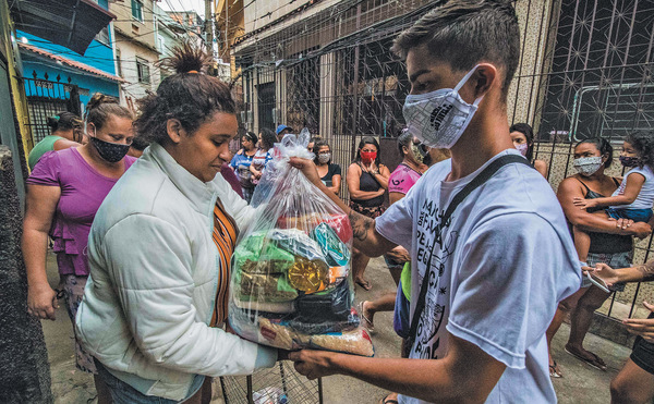 Young Rio favela residents, part of the grassroots Marcha das Favelas group, organize mutual aid to make up for the absence of the Brazilian state in tackling the crisis. Photo: Ellan Lustosa / Zuma / Alamy