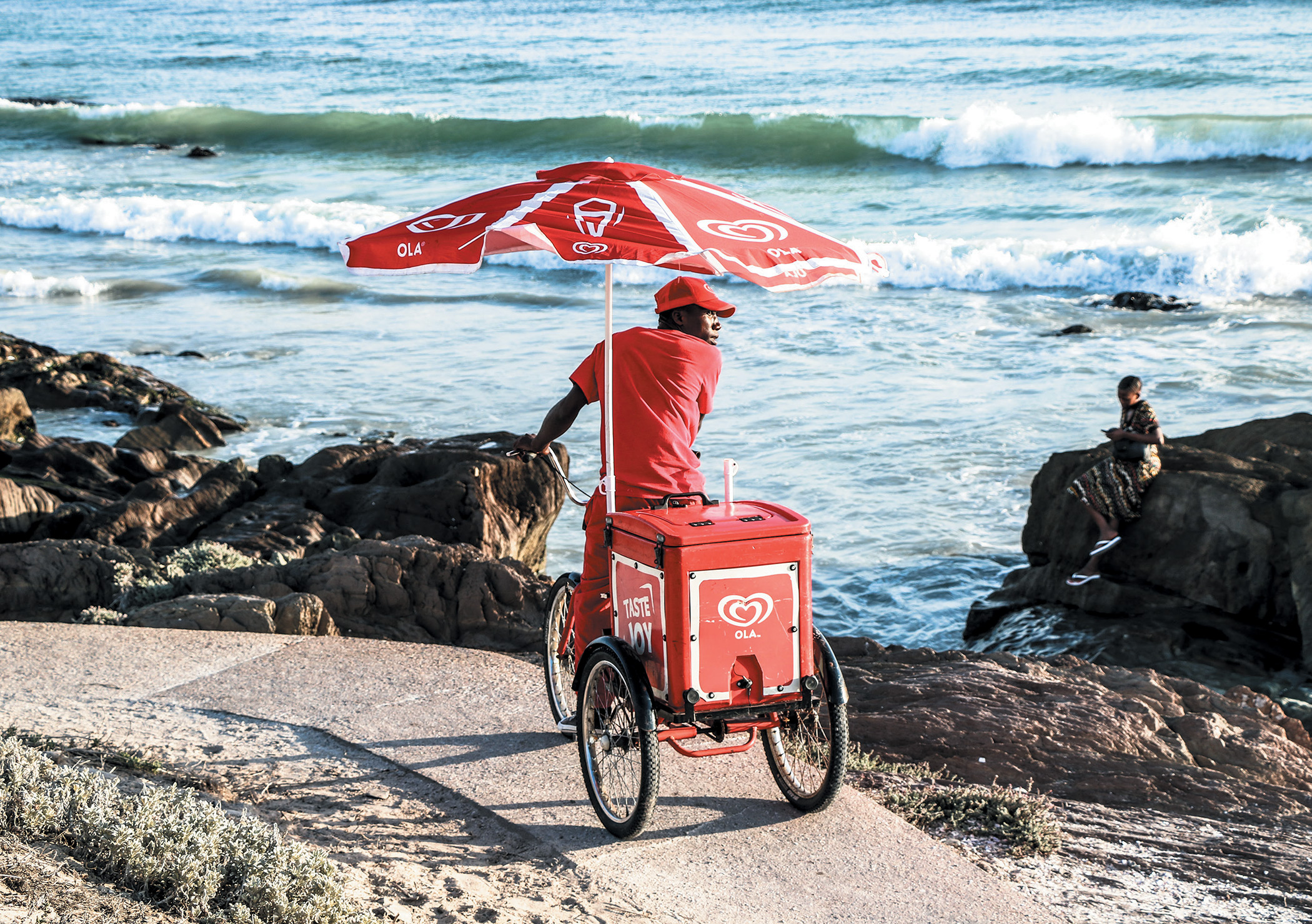 A man sells ice cream from an Ola cart in Bloubergstrand, South Africa. Ola is owned by Unilever. Rather than giving transnational corporations more power, a Global Green New Deal could be partly financed through climate reparations.