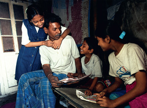 Homework time with Dad: Inderjeet Sharma, who runs a rickshaw workshop in Kolkata (formerly Calcutta), India, helps out with his children.