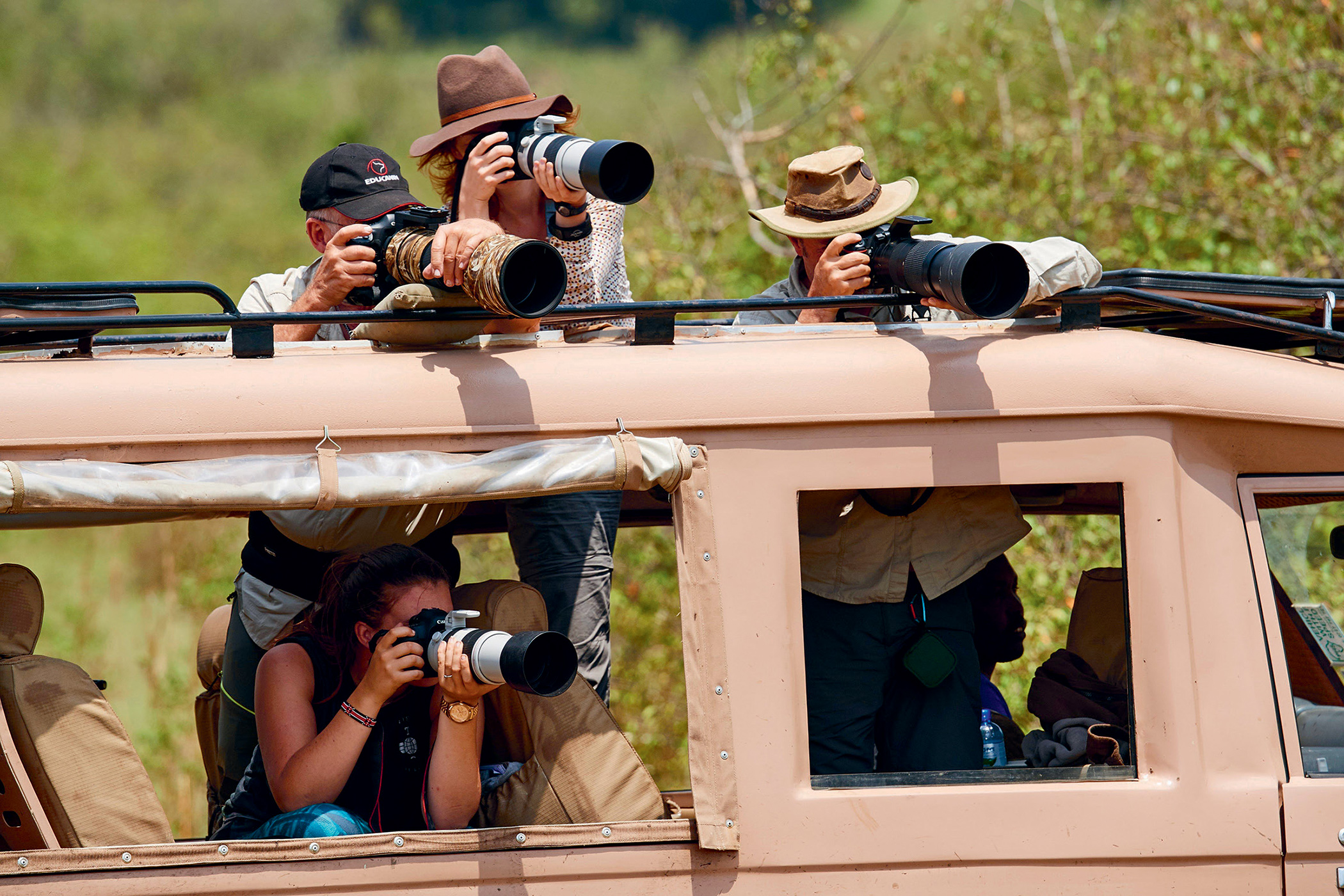 Tourists and photographers zoom in on wildlife at the Mara river during the great wildebeest migration, Maasai Mara National Reserve, Kenya.