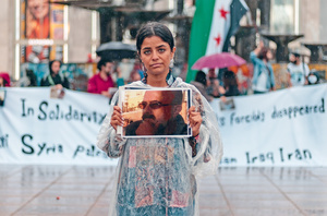 Wafa Ali Mustafa holds up a picture of her father during a demonstration on the International Day of the Disappeared, at Alexanderplatz, Berlin.Photo: Ahmad Kalaji