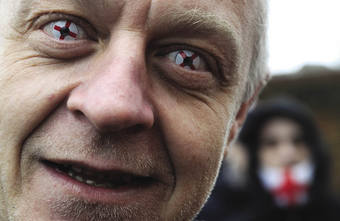 A hard-line look: an English Defence League supporter wears contact lenses sporting the St George cross – a symbol for some of white supremacy.