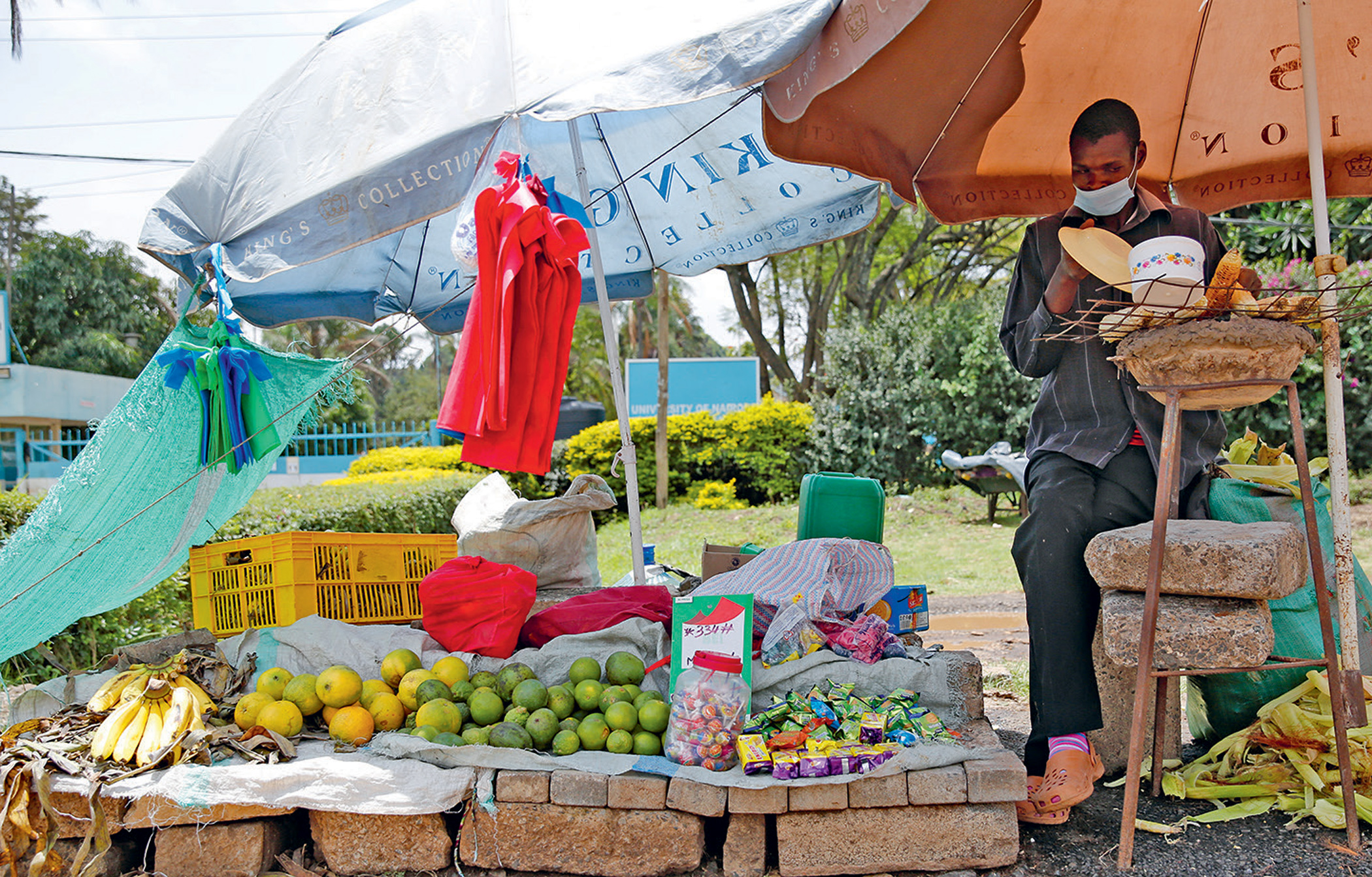 Geoffrey Arumba roasts maize at his open-air stall near the KFC restaurant at The Junction Mall in Nairobi. A meal at KFC costs what he earns in a day but he still aspires to take his family there.